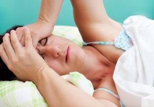 woman laying in bed with a headache