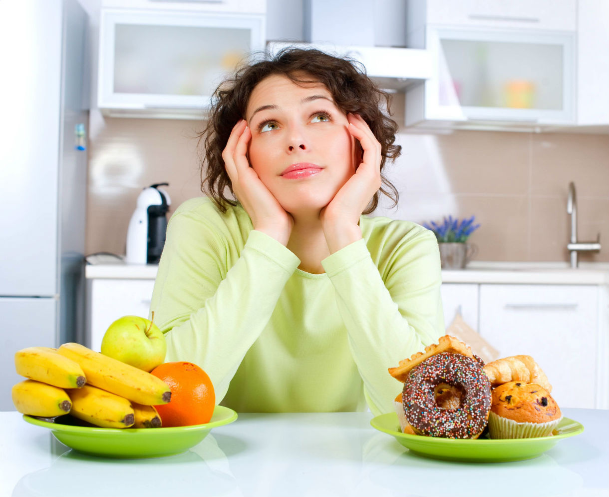 healthy - woman deciding btwn donuts and fruit