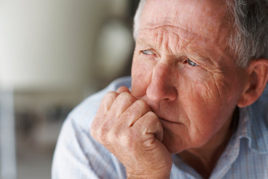 Closeup of an elderly man looking away in deep thought , depression