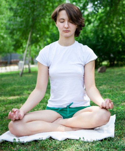 meditate - girl on grass meditating green shorts