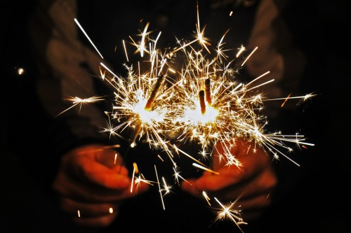 closeup of hands holding lit sparklers