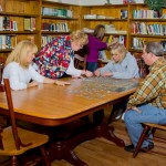 group of people doing a puzzle - Library Puzzle - St. Joseph Institute