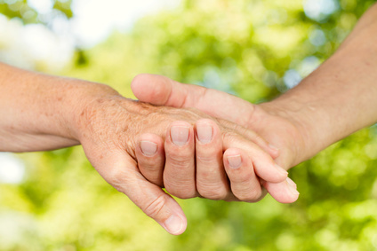 Closeup of old people hands holding together outdoors