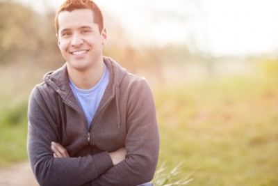 Portrait of a smiling young man standing outside