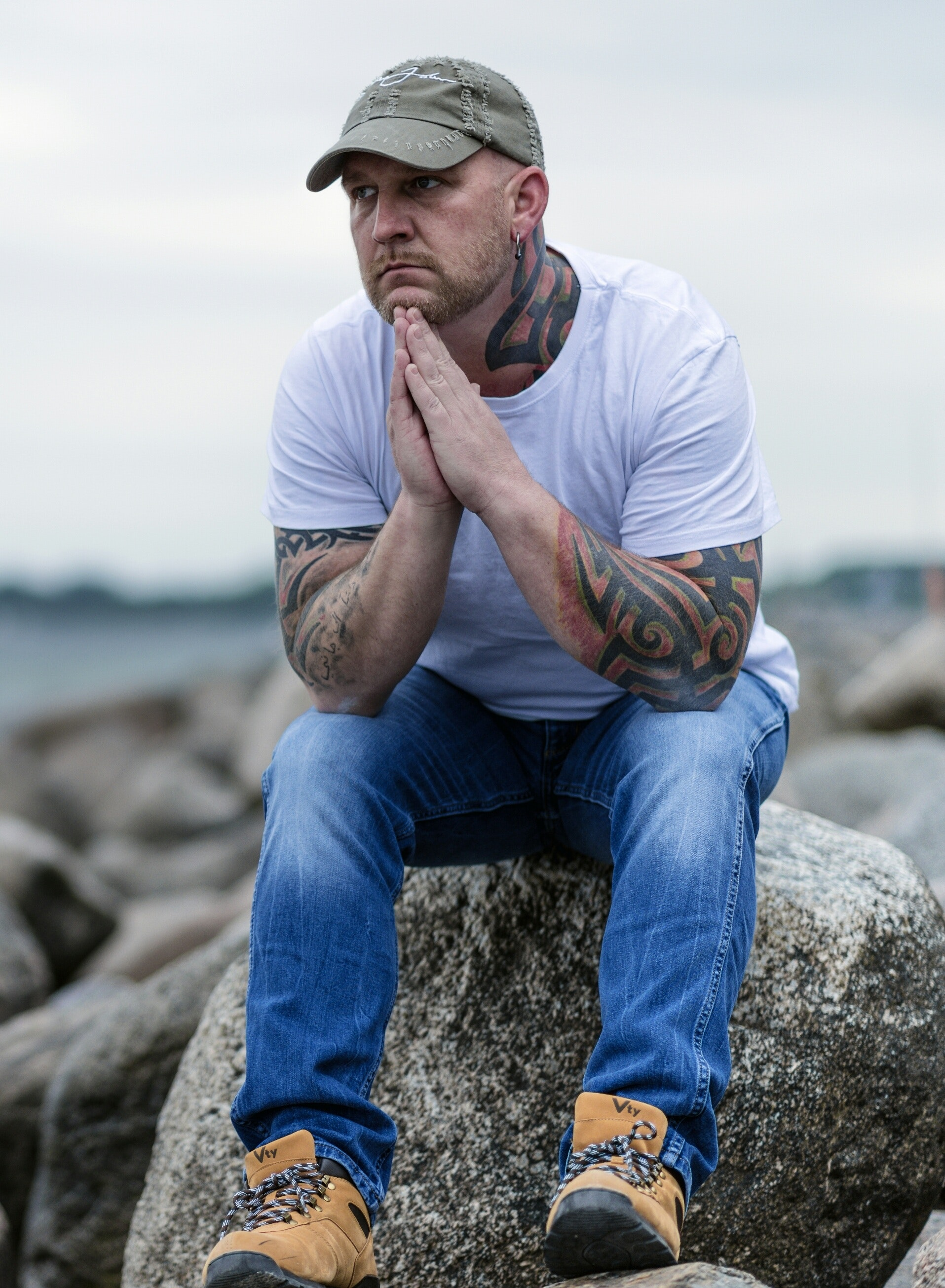man with tattoos sitting on large rock thinking