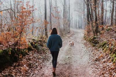 woman walking dog down path