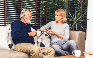 senior couple talking on couch at home