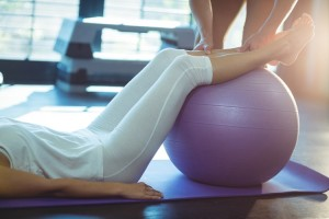 woman exercising with yoga ball and trainer - depression and anxiety