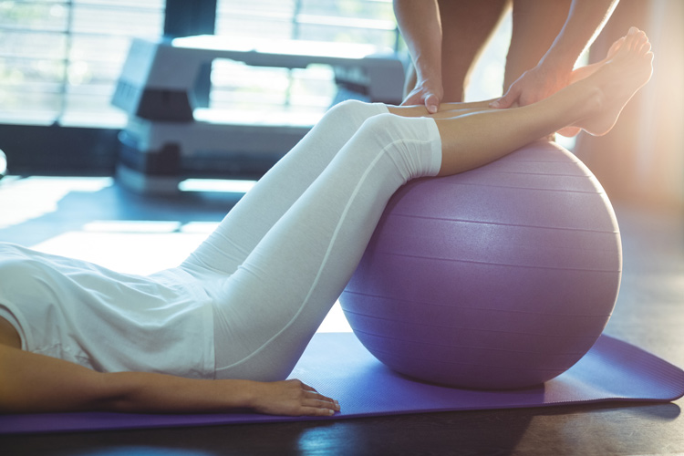 woman exercising with yoga ball and trainer