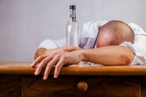 man passed out with liquor bottle - opioids