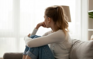 young blonde woman with ponytail hugging knees to chest on couch - trauma and addiction