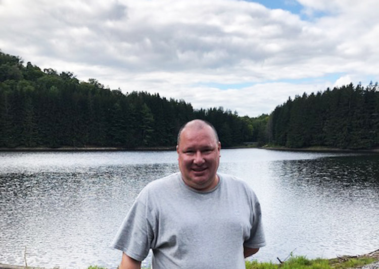 smiling man in grey shirt standing in front of lake - SJI Graduate Kris