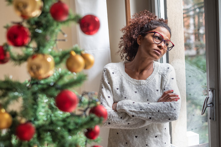 African American woman with arms crossed looking out the window at Christmas time - SAD