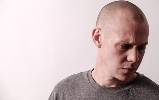 upset man with shaved head looking down - denial