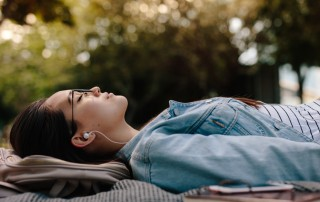 young woman lying down on blanket outside with headphones - sobriety first
