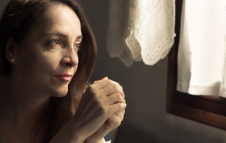 thoughtful woman looking out window of home - victim mentality