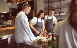 happy couple in kitchen with chef taking cooking class - sober date
