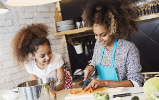 beautiful mother and daughter cooking in kitchen together - mother