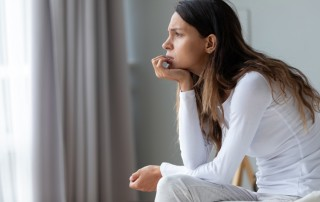 young woman sitting on the edge of her bed thinking - fear