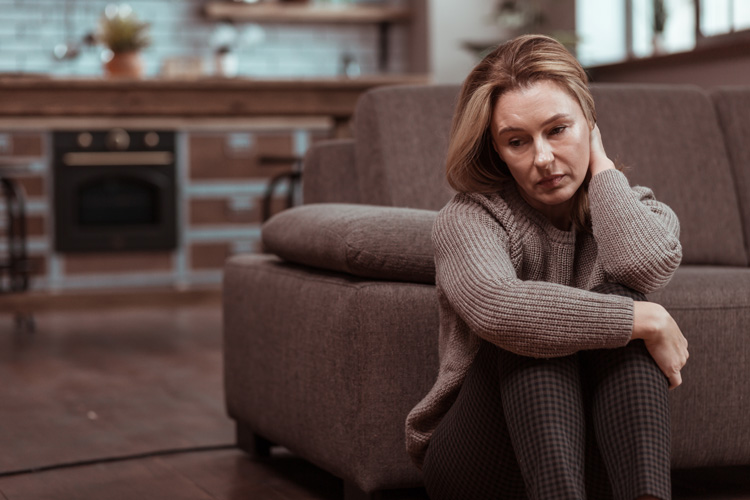 sad woman sitting on floor at home - your recovery