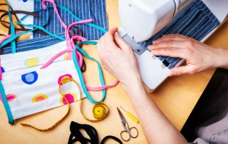 woman sewing homemade masks on sewing machine - stress