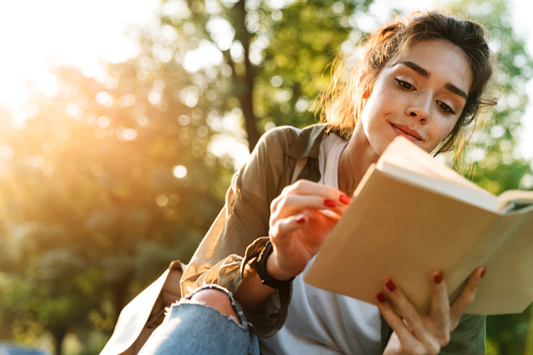 pretty young woman reading book outdoors