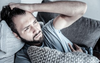 distressed man on couch at home - symptoms of addiction - covid-19