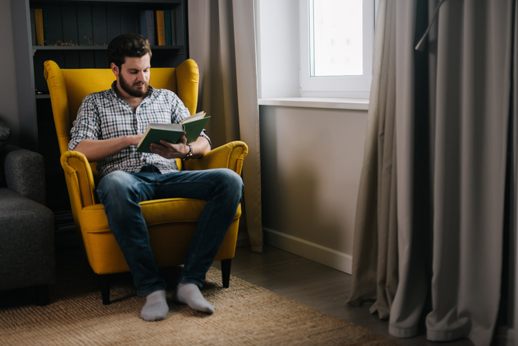 man sitting at home in yellow chair reading a book - mental health - COVID-19