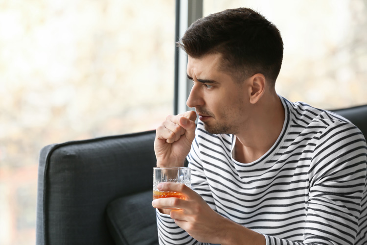 young man holding alcoholic drink about to cough - immune system