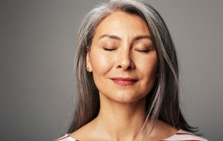 beautiful older woman with her eyes closed, smiling slightly - radical acceptance