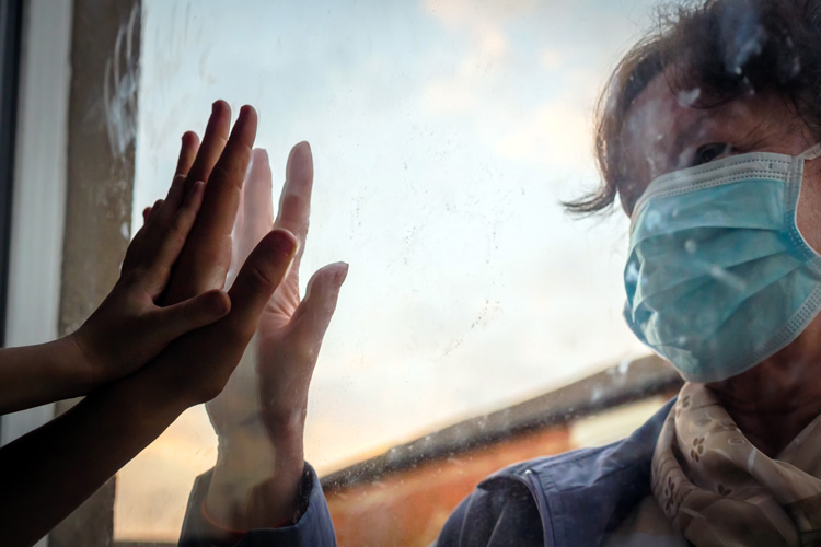 older woman in face mask holding her hand up to child's hand on window pane - mental health and pandemic