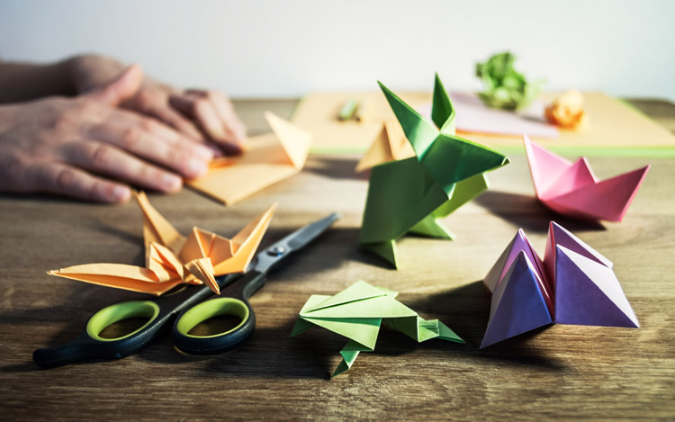 Origami crafts and supplies on wooden table - creativity