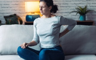 young woman sitting on couch, suffering with back pain - chronic pain