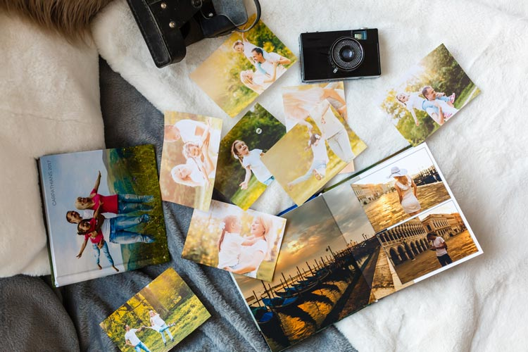photographs laid out on bed or table - grief