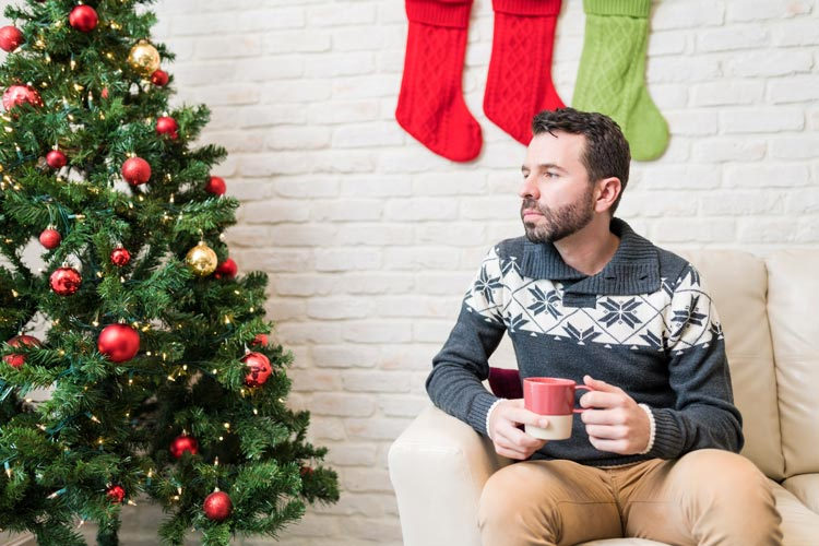 man in his thirties sitting alone next to Christmas tree drinking coffee or cocoa, thinking - loneliness