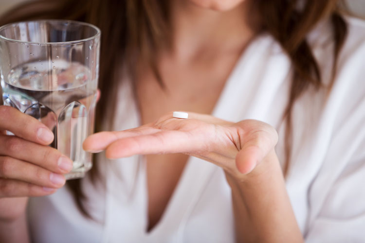 closeup of woman taking a white tablet - antidepressants and addiction recovery