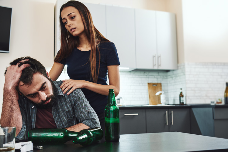 tired looking woman with her hands on the shoulders of her man who is sitting at a table full of empty beer bottles - codependent relationships